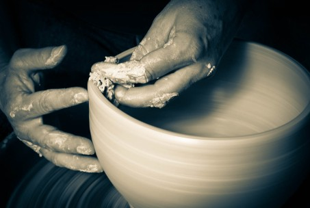 Potters hands making clay pot